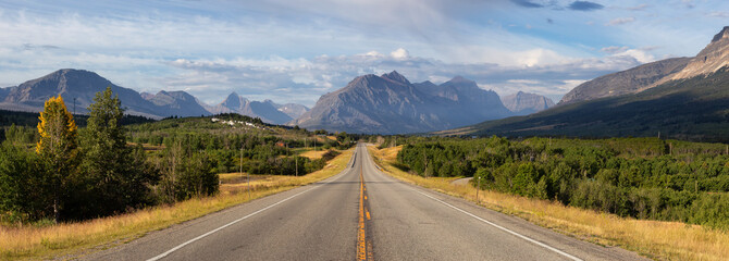 Wall Mural - Beautiful View of Scenic Highway with American Rocky Mountain Landscape in the background during a Cloudy Summer Morning. Taken in St Mary, Montana, United States.