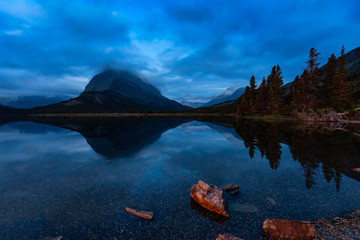 Wall Mural - Beautiful View of the reflection in the water with the Night Sky in the American Rockies. Taken in Swiftcurrent Lake, Glacier National Park, Montana, United States.