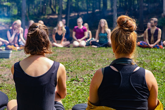 Diverse people enjoy spiritual gathering A closeup and rear view of two women, sitting around a campfire with like minded people in deep meditation during a shamanic retreat in nature.