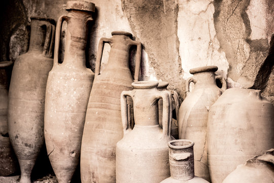 Antique ceramic jugs, pots and vases in ancient city Ercolano of roman times ruined by volcano Vesuvius in Italy