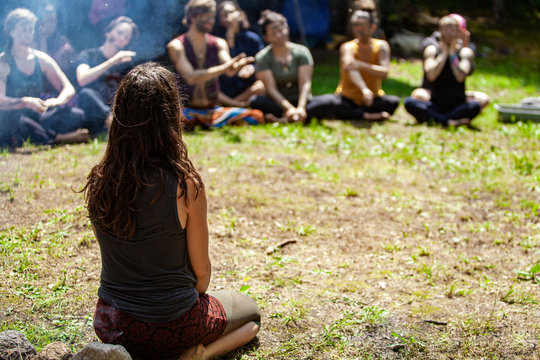 Diverse people enjoy spiritual gathering A close up and rear view of a shaman practitioner sitting on grass in a sacred forest clearing, teaching ancient traditions to blurry people in background.