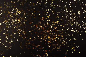 Gold foil confetti on black background. Flatlay.