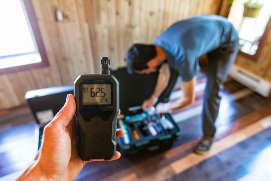 Indoor damp & air quality (IAQ) testing. A first person perspective of a person using an indoor air quality monitor device, checking for allergens, particles and CO2 during a domestic home inspection.