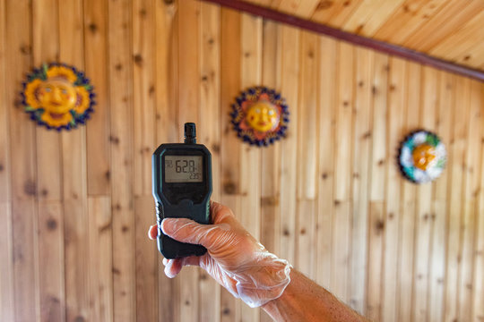 Indoor damp & air quality (IAQ) testing. A digital air monitoring device is seen close up in the hand of a person, showing a high reading to indicate airborne allergens, particles and CO2 in the home.