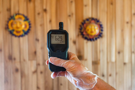 Indoor damp & air quality (IAQ) testing. A close up view of a home environmental quality inspector using a handheld air quality monitor with digital display showing a moderate level of pollutants.