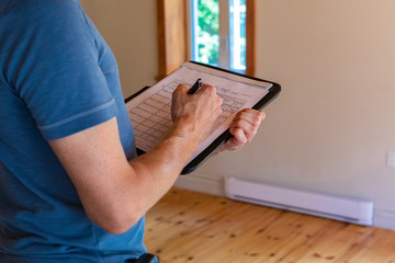 Indoor damp & air quality (IAQ) testing. A close up view on the muscular arm of a professional man wearing a short sleeved blue shirt, filling out papers during a home inspection, with copy-space.