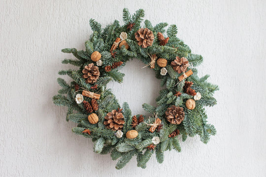 Christmas wreath made of natural fir branches  hanging on a white wall.  Wreath with natural ornaments: bumps, walnuts, cinnamon, cones. New year and winter holidays. Christmas decor