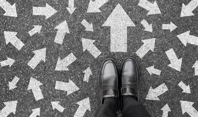 Feet and arrows on road background from above. Businessman standing on pathway with drawn white many direction arrows choice. Top view of A business man black shoes. Motivation and growth concept.