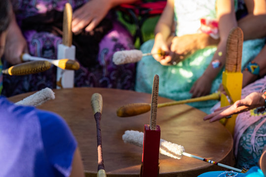 Sacred drums during spiritual singing. A close up view during a traditional singing circle where participants gather round a mother drum and play traditional native music, with copy space.