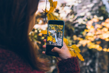 woman taking picture of autumn waterfall on the phone