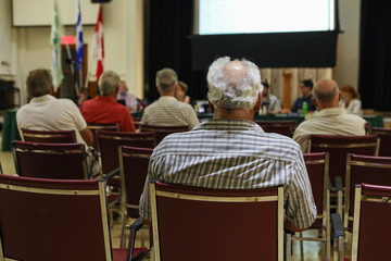 People attend local town hall meeting. A closeup and back view of an older man sitting indoors during a city hall legislation meeting, blurry attendees are seen in background with copy-space.