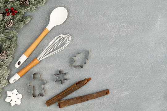 Utensils for Christmas baking with spoon, whisk, cookie cutters, cinnamon sticks and snow flake with snowy pine branches with cones over stone like background with copy space. Flat lay, top view.