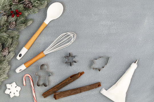 Utensils for Christmas cooking or baking with spoon, whisk, icing piping bag, cookie cutters, cinnamon sticks, candy cane and snow flake with fir branches over stone background, copy space flat lay