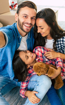 Our life is a gift. Family portrait of a man, his wife and their daughter who smiles and looks at her mother while laying on his lap.
