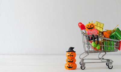 Halloween festival shopping concept. Halloween pumpkins with shopping cart on white background with copy space.