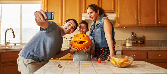 family taking selfie with jack-o-lantern for halloween