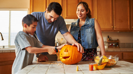 halloween activity - family carving pumpkin into jack-o-lantern
