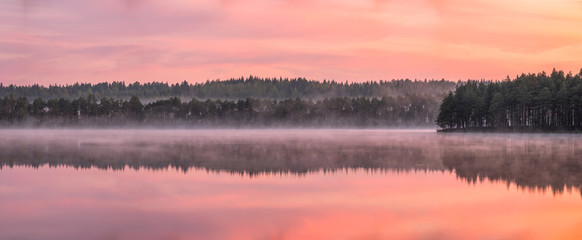 Beautiful sunrise landscape with misty mood and calm lake at foggy summer morning in Finland