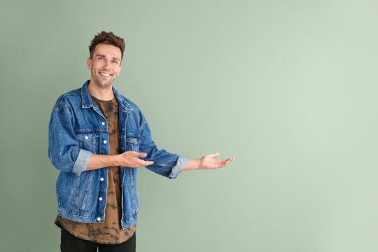 Handsome young man showing something on color background