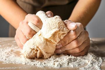 Woman kneading flour in kitchen, closeup