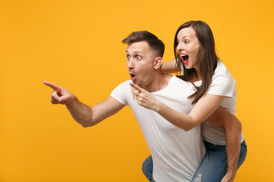 Shocked young couple in white t-shirts posing isolated on yellow orange background. People lifestyle concept. Mock up copy space. Giving piggyback ride to joyful sitting on back pointing finger aside.