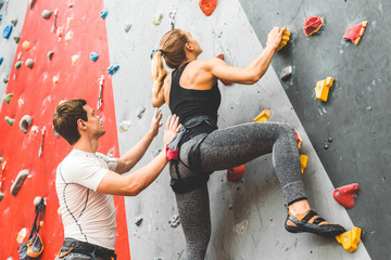 couple of athletes climber moving up on steep rock, climbing on artificial wall indoors. Extreme sports and bouldering concept
