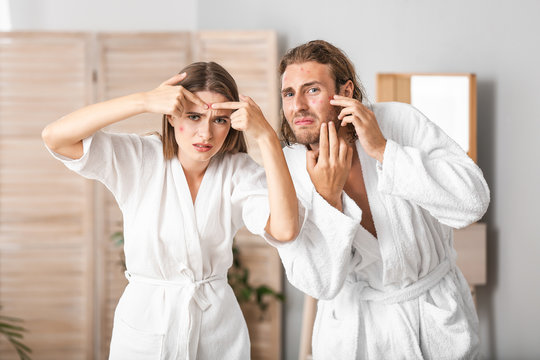 Portrait of young couple with acne problem at home