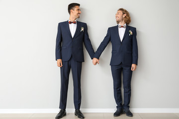 Portrait of happy gay couple on their wedding day against light wall