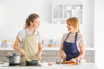 Young woman and her mother cooking together in kitchen