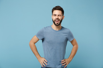 Young funny handsome man in casual clothes posing isolated on blue wall background, studio portrait. People sincere emotions lifestyle concept. Mock up copy space. Standing with arms akimbo, blinking.