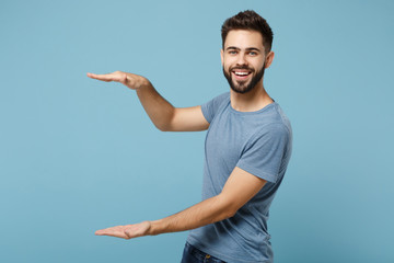 Young cheerful smiling man in casual clothes posing isolated on blue background, studio portrait. People lifestyle concept. Mock up copy space. Gesturing demonstrating size with vertical workspace.