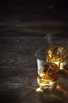 close up view of  two glasses with ice and whiskey on wooden background