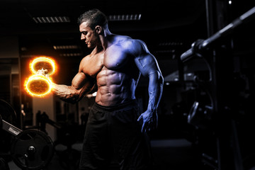 Muscular athletic bodybuilder fitness model training arms with dumbbells on fire in gym. Concept sport photo of exercises in gym