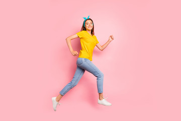 Full body photo of cheerful millennial running wearing yellow t-shirt isolated over pink background