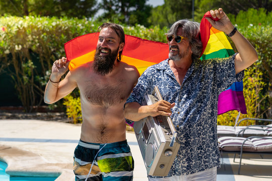 Portrait of a gay couple walking by the pool with a rainbow flag.