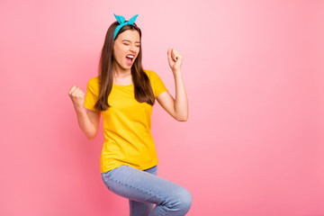 Portrait of cheerful youth raising her fists shouting yeah wearing yellow t-shirt isolated over pink background