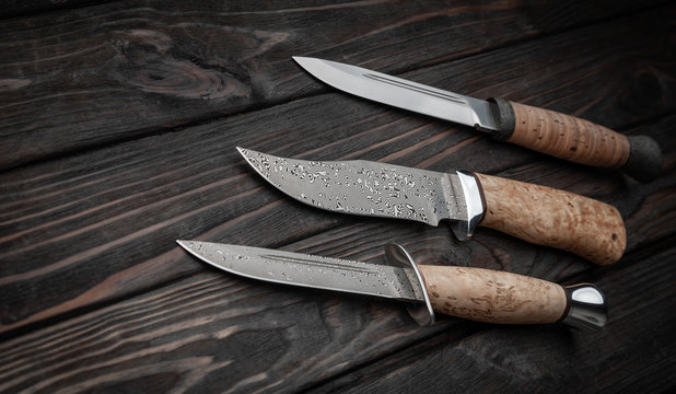 Hunting bowie knife with a wooden handle on dark wooden background. Steel arms weapon. top view