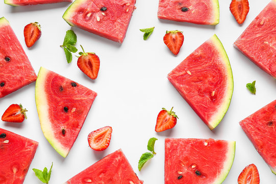 Many slices of watermelon with strawberry and mint on white background