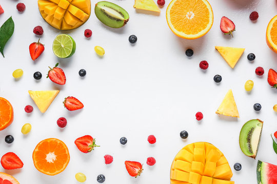 Frame made of ripe fruits and berries on white background