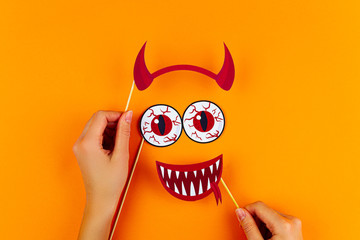 Funny face of monster with red horns, blood eyes and vampire smile on orange background. Female hands are holding paper photo props on canvas. Party accessories for celebration happy halloween.