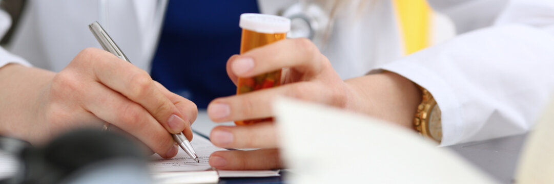 Female medicine doctor hand hold jar of pills and write prescription to patient at worktable. Panacea and life save prescribing treatment legal drug store concept. Empty form ready to be used
