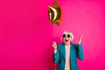 Portrait of her she nice-looking attractive lovely crazy overjoyed cheerful cheery gray-haired lady holding balloon having fun isolated on bright vivid shine vibrant pink fuchsia color background