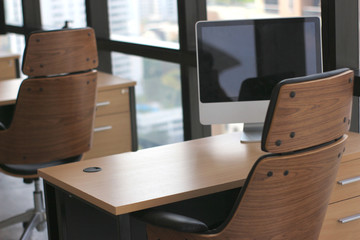 selective focus at wooden table desk in office business room with big computer monitor and windows background