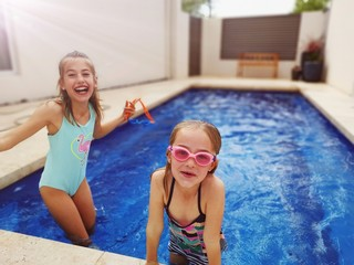 two kids playing in their pool at home