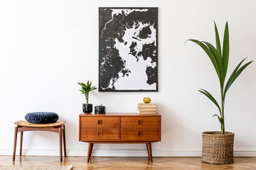 Stylish and retro living room with design vintage wooden commode, footrest, tropical plants, books and elegant personal accessories. Mock up poster map on the wall. Template. Home decor.