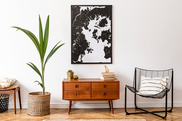 Stylish interior design of living room with wooden retro commode, chair, tropical plant in rattan pot, basket and elegant personal accessories. Mock up poster frame on the wall. Template. Home decor.