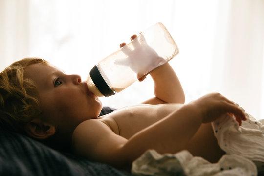 Kleiner Junge trinkt Milch aus einer Flasche
