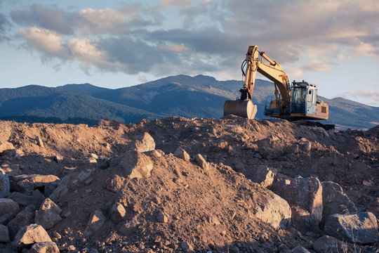 Excavator moving stone and earth