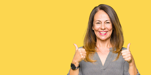 Beautiful middle age business woman success sign doing positive gesture with hand, thumbs up smiling and happy. Looking at the camera with cheerful expression, winner gesture.