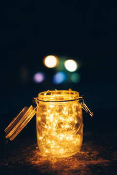 Fairy light in vintage hipster glass jar with blur bokeh dark background.